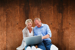 Composite image of happy mature couple using laptop Royalty Free Stock Photo