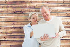 Composite image of happy mature couple using laptop Stock Photography