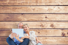Composite image of happy mature couple using tablet pc Royalty Free Stock Photography