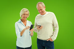 Composite image of happy mature couple using their smartphones royalty free stock photos