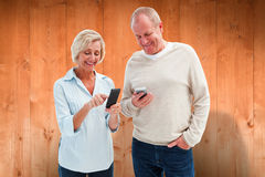 Composite image of happy mature couple using their smartphones Stock Images