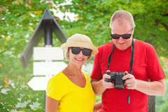 Composite image of happy mature couple wearing sunglasses. Happy mature couple wearing sunglasses against blank sign boards against trees Stock Images