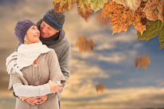 Composite image of happy mature couple in winter clothes embracing Stock Photo