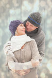 Composite image of happy mature couple in winter clothes embracing Royalty Free Stock Photos