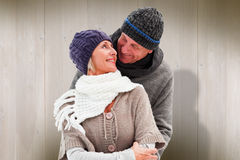 Composite image of happy mature couple in winter clothes embracing. Happy mature couple in winter clothes embracing against wooden planks Stock Image