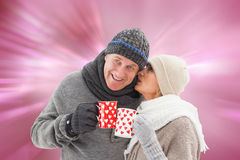 Composite image of happy mature couple in winter clothes holding mugs. Happy mature couple in winter clothes holding mugs against digitally generated love heart Royalty Free Stock Photos