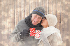 Composite image of happy mature couple in winter clothes holding mugs Royalty Free Stock Photos