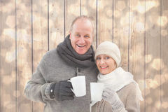 Composite image of happy mature couple in winter clothes holding mugs Stock Photos