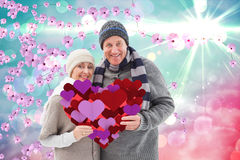 Composite image of happy mature couple in winter clothes holding red heart. Happy mature couple in winter clothes holding red heart against digitally generated royalty free stock image