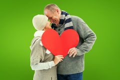 Composite image of happy mature couple in winter clothes holding red heart Royalty Free Stock Image
