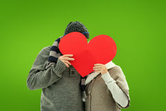 Composite image of happy mature couple in winter clothes holding red heart Royalty Free Stock Photos