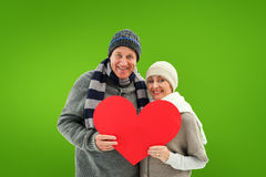 Composite image of happy mature couple in winter clothes holding red heart Stock Photos