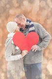 Composite image of happy mature couple in winter clothes holding red heart Stock Image