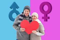 Composite image of happy mature couple in winter clothes holding red heart Royalty Free Stock Photo