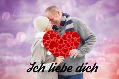 Composite image of happy mature couple in winter clothes holding red heart. Happy mature couple in winter clothes holding red heart against pink and purple girly royalty free stock images