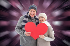 Composite image of happy mature couple in winter clothes holding red heart Royalty Free Stock Photography