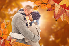 Composite image of happy mature couple in winter clothes hugging Royalty Free Stock Photo