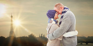 Composite image of happy mature couple in winter clothes hugging Stock Images