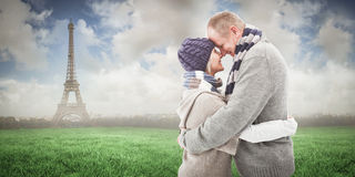 Composite image of happy mature couple in winter clothes hugging Royalty Free Stock Image