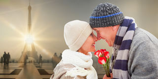 Composite image of happy mature couple in winter clothes with roses Stock Photos