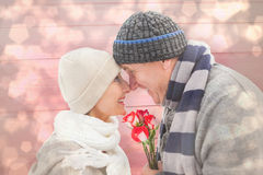Composite image of happy mature couple in winter clothes with roses Stock Image