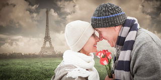 Composite image of happy mature couple in winter clothes with roses Royalty Free Stock Image