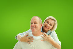 Composite image of happy mature man giving piggy back to partner Stock Photography
