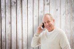 Composite image of happy mature man on the phone Stock Image