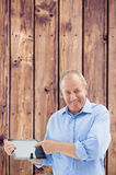 Composite image of happy mature man pointing to his tablet pc Royalty Free Stock Images