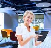 Composite image of happy mature woman pointing to tablet pc Stock Photography