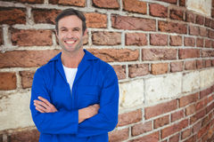 Composite image of happy mechanic with arms crossed over white background Royalty Free Stock Photography
