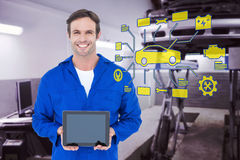 Composite image of happy mechanic holding digital tablet Royalty Free Stock Photos