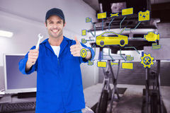 Composite image of happy mechanic holding spanner. Happy mechanic holding spanner against auto repair shop Stock Photos