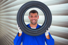 Composite image of happy mechanic looking through tire Royalty Free Stock Photos