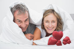 Composite image of happy middle aged couple under the duvet Stock Images