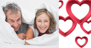 Composite image of happy middle aged couple under the duvet Royalty Free Stock Image