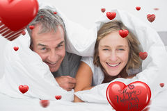 Composite image of happy middle aged couple under the duvet Stock Photos