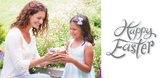 Composite image of happy mother and daughter collecting easter eggs Stock Photography