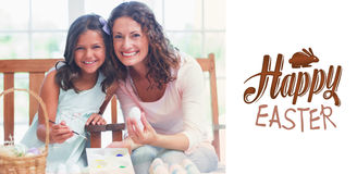 Composite image of happy mother and daughter painting easter eggs Royalty Free Stock Image