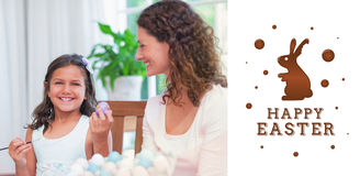 Composite image of happy mother and daughter painting easter eggs Stock Photography
