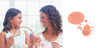 Composite image of happy mother and daughter painting easter eggs Royalty Free Stock Photo