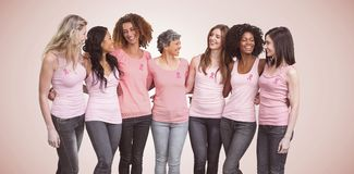 Composite image of happy multiethnic women standing together with arm around. Happy multiethnic women standing together with arm around against neutral stock photo