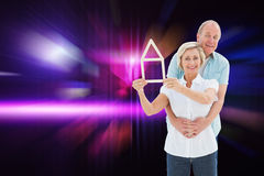 Composite image of happy older couple holding house shape Royalty Free Stock Photography