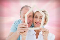 Composite image of happy older couple holding house shape. Happy older couple holding house shape against digitally generated pink girly design Royalty Free Stock Photo