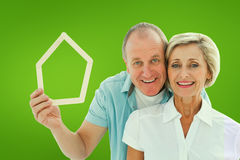 Composite image of happy older couple holding house shape. Happy older couple holding house shape against green vignette Royalty Free Stock Photos