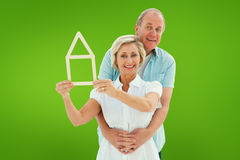 Composite image of happy older couple holding house shape. Happy older couple holding house shape against green vignette Royalty Free Stock Photo