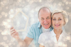 Composite image of happy older couple holding house shape. Happy older couple holding house shape against light glowing dots design pattern Royalty Free Stock Image