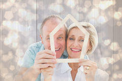 Composite image of happy older couple holding house shape. Happy older couple holding house shape against light glowing dots design pattern Royalty Free Stock Photo