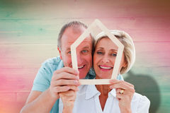 Composite image of happy older couple holding house shape. Happy older couple holding house shape against pink and green planks Royalty Free Stock Photos