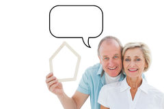 Composite image of happy older couple holding house shape Royalty Free Stock Images